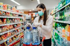 Free Buyer Wearing A Protective Mask.Shopping During The Pandemic.Emergency To Buy List.Water Supplies Shortage.Panic Buying During Stock Photography - 176624992