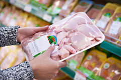Buyer woman chooses chicken meat in shop Royalty Free Stock Photo