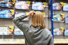 Buyer woman and TV in store. Buyer woman selects TV in store stock photo