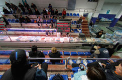 Buyers bidding for fish captures on a fish market. Authorized buyers sit and bid for the boxes of daily fish captures offered on a local fish market in the Stock Image