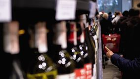 Buyers choose alcoholic beverages on shelves of supermarket in the wine and vodka department