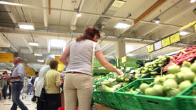 Buyers choose vegetables and fruit in a supermarket. Buyers choose fresh vegetables and fruit in a supermarket stock footage