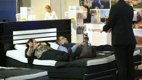 Buyers are experiencing a new orthopedic bed with remote control. HELSINKI, FINLAND - MARCH 17, 2017: Buyers are experiencing a new orthopedic bed with remote stock video