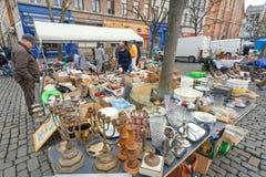 Buyers on flea market with old metal candlesticks, bargains, antique stuff, vintage decor and retro utensils. BRUSSELS, BELGIUM - APR 3: Buyers on flea market Stock Image