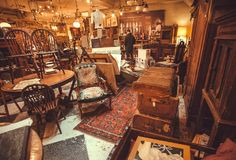 Buyers inside the antique shop with utensils, lamps, souvenirs and retro furniture Royalty Free Stock Photography