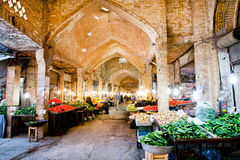 Buyers select fresh fruits and vegetables under the ancient vaults of Eastern Bazaar. Royalty Free Stock Image