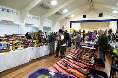 Buyers and sellers at a gun show in NZ. A large number of rifles and shotguns on display at a gun show in New Zealand. Some are for sale, others are just Stock Image
