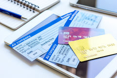 Buying airline tickets online with credit cards on table background Stock Images