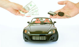 Buying a car. A female hand giving money,a black sports car and male hand holding key isolated on a white background Stock Images