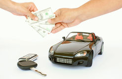 Buying car. A key a black sports car and female hand giving money to a male hand isolated on a white background Royalty Free Stock Images