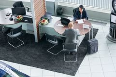 Buying a car. Businessman sitting at office in auto salon and buying a new car stock photography