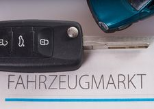 Buying a car. Car key and vehicle market newspaper Royalty Free Stock Photos