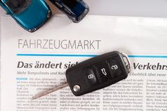 Buying a car. Car key and vehicle market newspaper Stock Photo