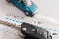Buying a car. Car key and vehicle market newspaper Royalty Free Stock Photo