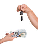 Buying a car. Male hand holding a car key and handing it over to another person.Woman holding dollars Royalty Free Stock Image