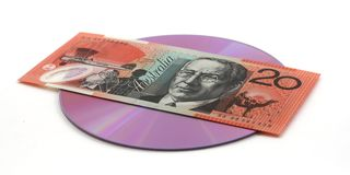 Buying CD, DVD. 20 dollar note (Australian) over a CD or DVD, isolated over white Stock Images