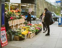 Buying flowers in London intersection street people florist. London, United Kingdom - Mar 10 2017: Couple buying flowers at flower florist kiosk on the street in Stock Photos