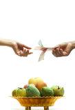 Buying fruits. Hand the money to buy fruits in the tray Stock Photography