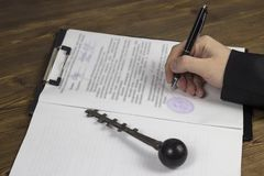 Buying a garage, garage key, pen, contract, hand contract stock photos