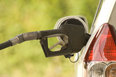 Buying Gasoline. A black gasoline nozzle in the gas tank of a car being filled up Royalty Free Stock Photos
