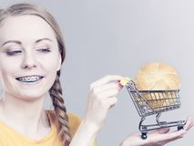 Woman holding shopping cart with bread. Buying gluten food products concept. Woman holding shopping cart trolley with small piece of bread bun Royalty Free Stock Photography