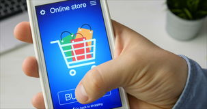 Buying goods in online store using smartphone application stock footage