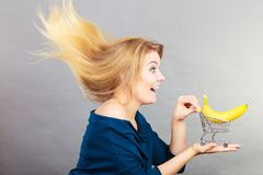 Woman holding shopping cart with banana inside. Buying healthy food, vegetarian, gluten free, vegan products. Woman holding shopping cart with banana inside Royalty Free Stock Image