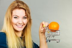 Woman holding shopping cart with orange inside. Buying healthy food, vegetarian, gluten free, vegan products. Woman holding shopping cart with orange inside Stock Image