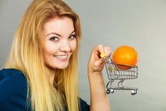 Woman holding shopping cart with orange inside Stock Image