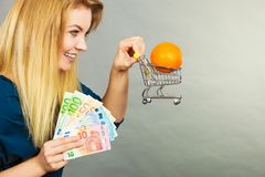 Woman holding shopping cart with orange inside Stock Photos