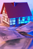 Buying a house. US dollars and mini house with colorful light Stock Image