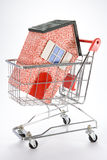 Buying A House. Model house in a shopping trolly Stock Photography