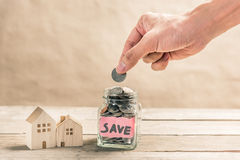 Buying house concept. Male hand putting coin in glass jar of coin for saving money for buying house Stock Photos