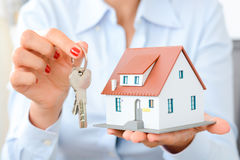 Buying a house concept with woman hands holding a model house and keys. Buying a house concept with woman hands holding a model house and house keys Stock Photo