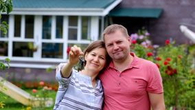 Buying house concept. Woman with her husband holding keys from new house. stock video footage