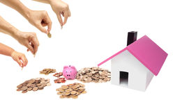 Buying a house. Grandmother, father, mother, and baby in the family do saving money in pink piggy banks for buying a house Royalty Free Stock Photo