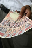 Buying with indian currency. Close up of a  hand paying in indian currency with thousand rupee notes Royalty Free Stock Photo