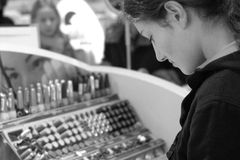 Buying makeup. Young girl looking to buy new makeup Royalty Free Stock Photography
