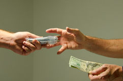 Buying marijuana drugs illegal sale for cash money. Closeup of a drug deal showing a man handing over a bag of drugs to the man with the money in his hand, he is stock photography