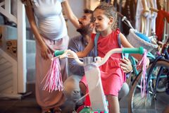 Buying new bicycle for little girl in bike shop. Buying new bicycle for happy little girl in bike shop royalty free stock image