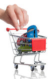 Buying a new car. A shopping cart ans some cars on a white background Royalty Free Stock Photos