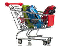 Buying a new car. A shopping cart ans some cars on a white background Stock Image