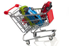 Buying a new car. Some cars in a shopping cart on a white background Royalty Free Stock Photography