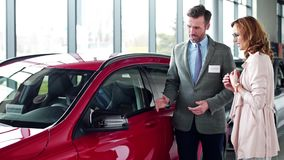 Buying new car. Car dealer talking with woman about cars details stock video footage