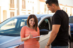 Buying a new car for myself. Happy young Hispanic women signing a financing plan for buying her brand new car Stock Images