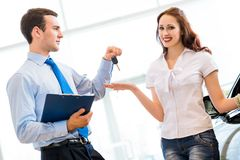 Buying a new car. Pretty women receives the keys to a new car from a sales manager Stock Photos
