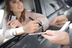 Buying new car by woman. Modern way of signing contract of buying car Royalty Free Stock Photography