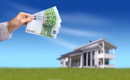 Buying new house. Concept. Hand and money on the foreground and new big house on the background royalty free stock photo