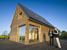 Buying  new house. A man and woman standing next to a new house with an interesting wooden elevation, negotiating and talking Stock Images
