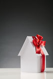 Buying a New House. Conceptual image about property ownership, buying a new house - a white paper house with a red ribbon with copy space above it stock image